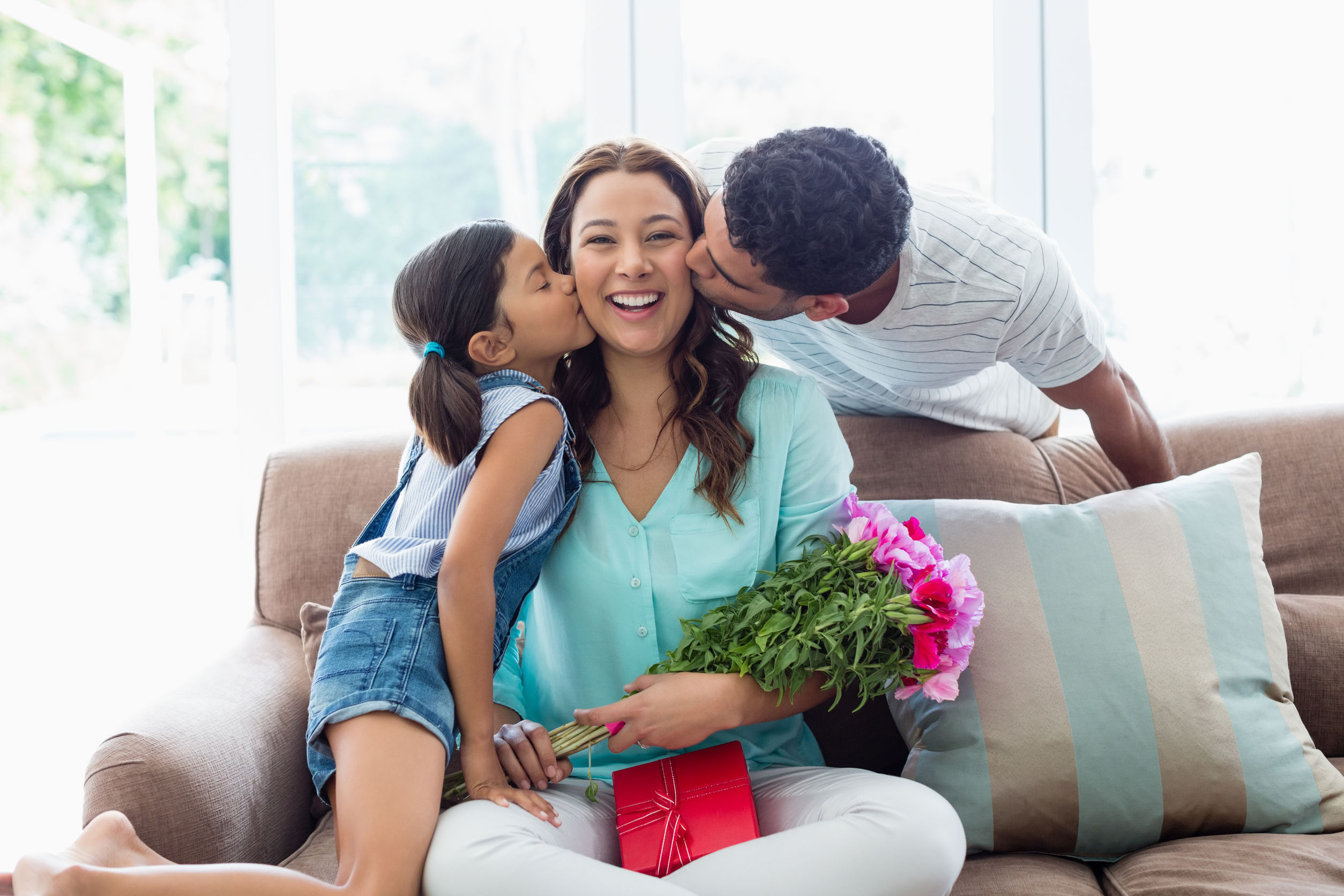Mother receiving flowers, gift and a kiss for Valentine's Day